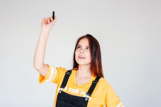 Jovem estudante sorridente garota trabalhador com cabelos longos escuros, vestindo uma camiseta amarela