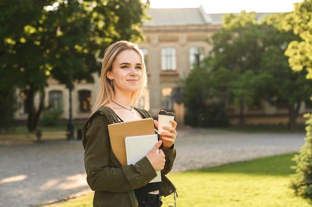 Jovem estudante sorridente segurando café para viagem no parque perto da faculdade