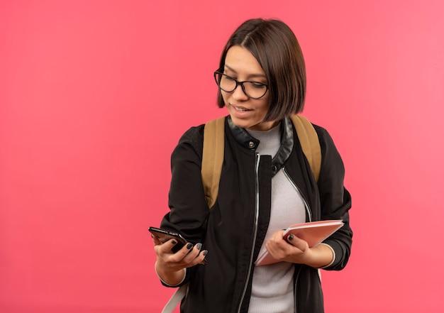 Jovem estudante sorridente usando óculos e bolsa traseira segurando um bloco de notas e um celular, olhando para o telefone isolado na parede rosa