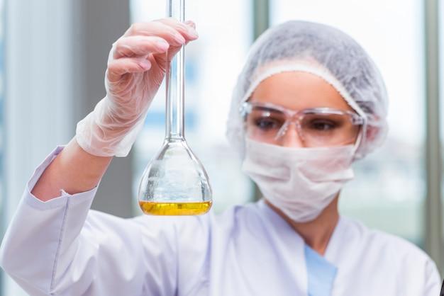 Jovem estudante trabalhando com soluções químicas no laboratório