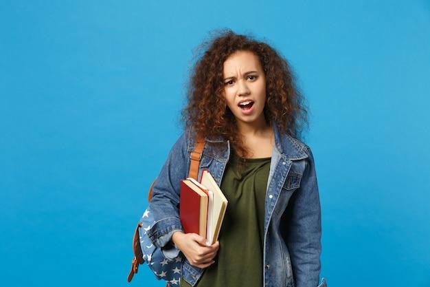 Jovem estudante triste com roupas jeans e mochila segurando livros isolados na parede azul