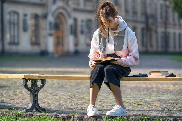 Jovem estudante universitária estudando ao ar livre