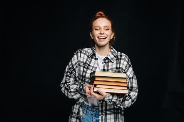 Jovem estudante universitária rindo segurando livros e olhando para a câmera