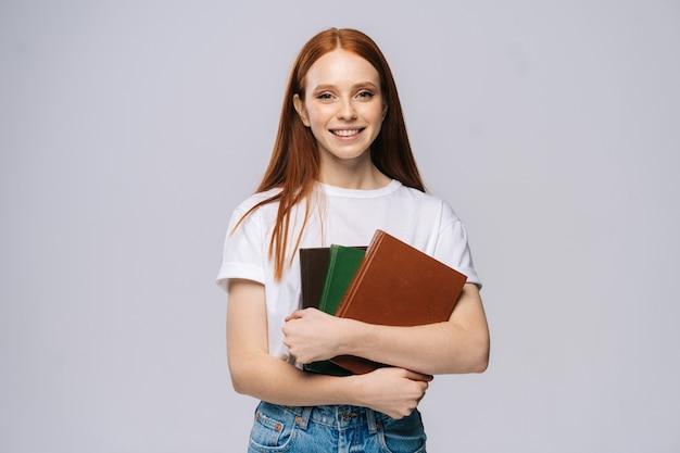 Jovem estudante universitária sorridente, vestindo camiseta e calça jeans, segurando um livro