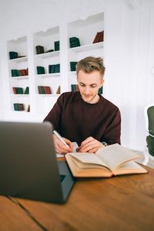 Jovem estudante universitário, caucasiano, estudando com um laptop a distância, preparando-se para o exame.