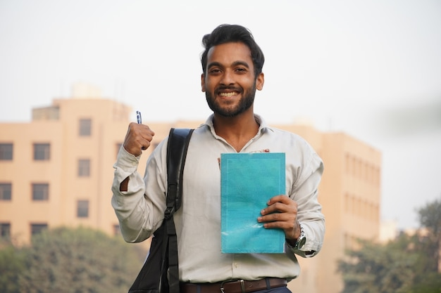 Jovem estudante universitário com livros e caneta e em pé sobre o prédio da colagem
