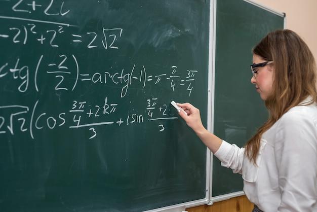 Jovem estudante universitário escrevendo exercícios matemáticos no quadro-negro durante uma aula. educação