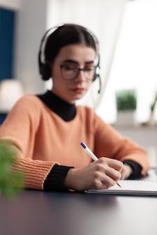 Jovem estudante universitário escrevendo informações de comunicação no caderno para exame escolar online usando a plataforma de e-learning. aluno com fone de ouvido fazendo a lição de casa enquanto está sentado à mesa na sala de estar