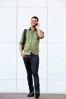 Jovem estudante universitário no telefonema com mochila