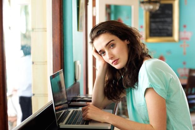 Jovem estudante universitário sentado no café com laptop