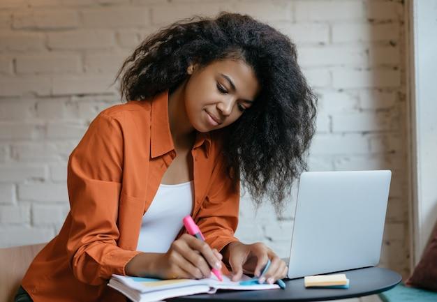 Jovem estudante usando laptop, anotando, estudando em casa, ensino a distância