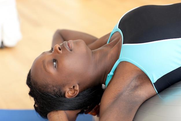 Jovem étnica trabalhando com uma bola de pilates