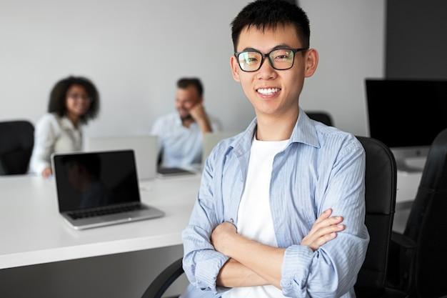 Jovem étnico de braços cruzados, sorrindo para a câmera enquanto trabalhava como estagiário no escritório de uma empresa moderna