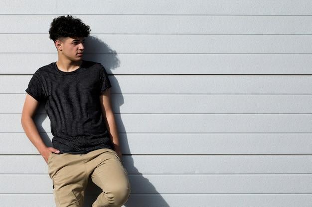 Jovem étnico encaracolado com as mãos nos bolsos, encostado na parede cinza