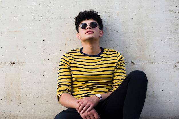 Jovem étnico encaracolado em óculos de sol, encostado na parede de concreto cinza