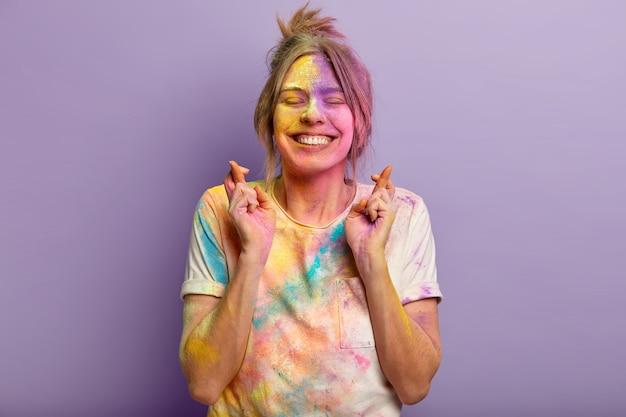 Jovem europeia alegre com expressão facial satisfeita, concentra-se no desejo, cruza os dedos, suja com o pó colorido de holi, espera por cima da parede roxa, vem no festival de cores com os amigos.