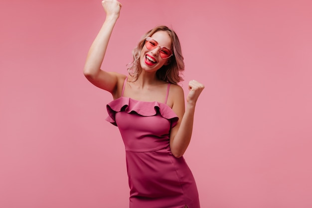 Jovem europeia alegre de óculos de sol dançando na parede rosada