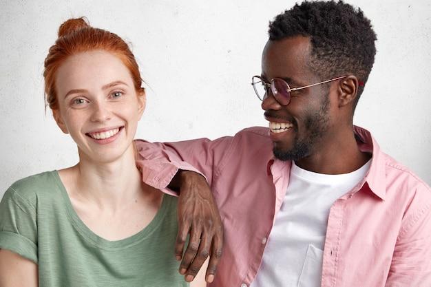Jovem europeia alegre e bonita com um nó no cabelo ruivo, vestida casualmente, passa bons momentos na companhia de um lindo