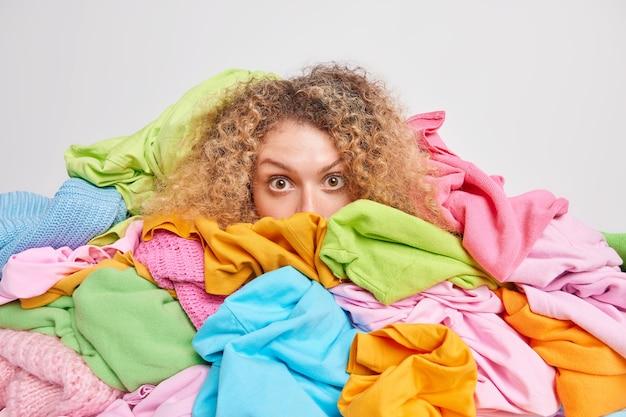 Jovem européia de cabelos cacheados impressionada escondida atrás de uma pilha de roupas multicoloridas indo lavar a roupa em casa isolada sobre o branco