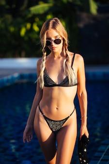 Jovem europeia em forma de mulher pequena e magra com duas tranças em um biquíni preto moderno e brilhante à beira da piscina