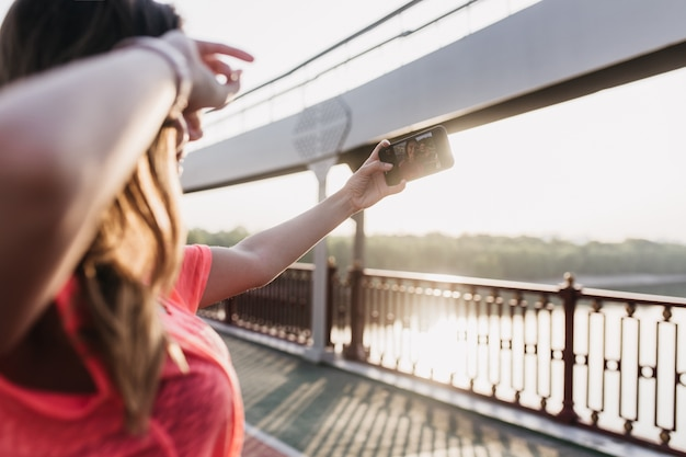Jovem europeia fazendo selfie após o treino. garota alegre tirando foto de si mesma na manhã ensolarada.
