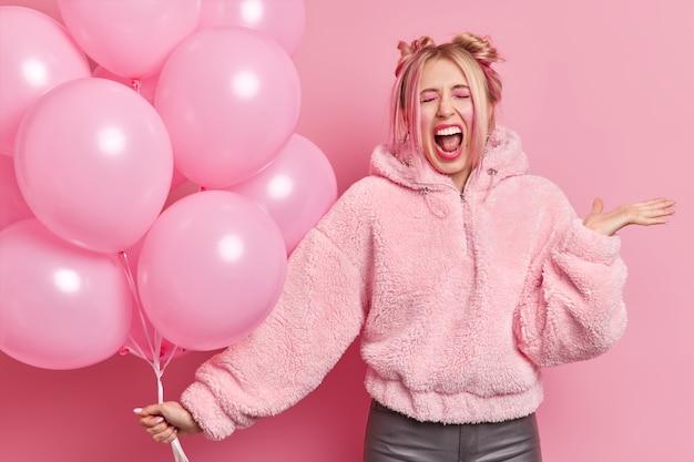 Jovem europeia loira emocional exclama com a boca bem aberta, vestida com um casaco de pele, levanta a palma da mão segurando um monte de balões de hélio inflados