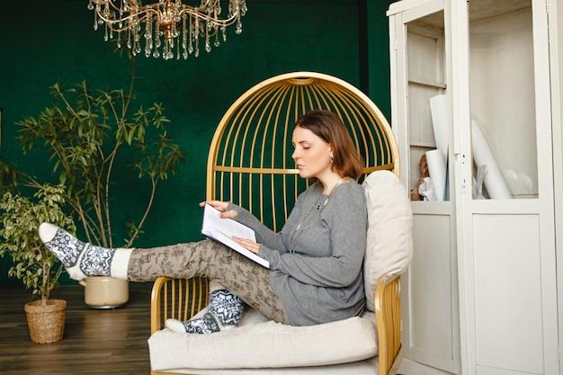 Jovem europeia morena com roupas de casa e meias quentes, sentada em uma cadeira em uma sala