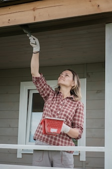 Jovem europeia pintando a varanda de uma nova casa de madeira