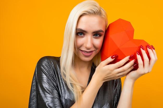 Jovem europeia segurando um coração vermelho nas mãos em uma parede laranja