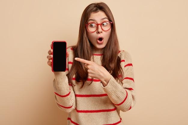 Jovem europeia surpreendida abre a boca de admiração, aponta para o celular com uma tela em branco para o modelo de conteúdo, design, usa um macacão bege com listras vermelhas, isolado sobre a parede marrom