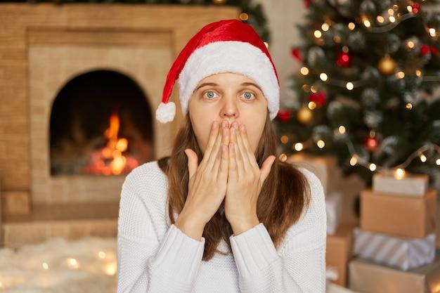 Jovem européia usa chapéu de papai noel e suéter branco, fica em casa por causa da decoração de natal, cobre a boca com as mãos, muito surpresa, posa com lareira e árvore de natal
