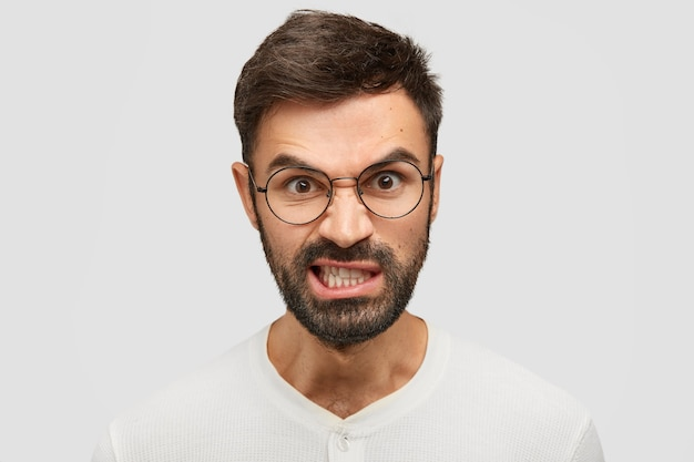 Jovem europeu aborrecido trinca os dentes de irritação, tem uma expressão furiosa e levanta as sobrancelhas de raiva