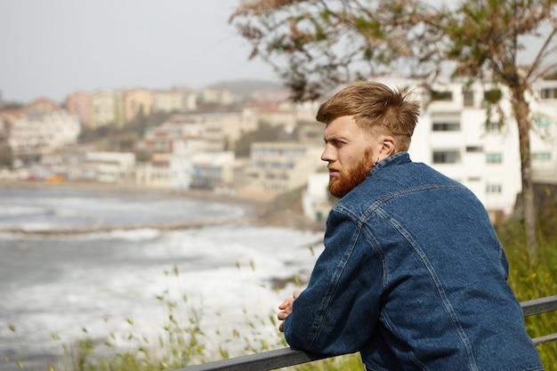 Jovem europeu atraente e pensativo com longa barba ruiva posando ao ar livre