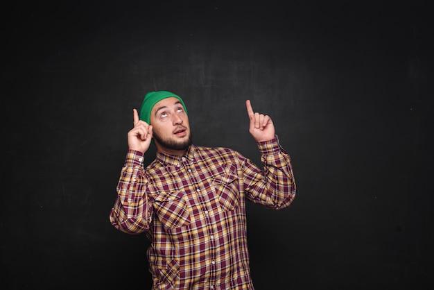 Jovem europeu com barba com chapéu de malha verde, parece surpreso e perplexo. mostrando os dedos para cima e para o lado direito. fundo preto, espaço de cópia em branco para texto ou anúncio