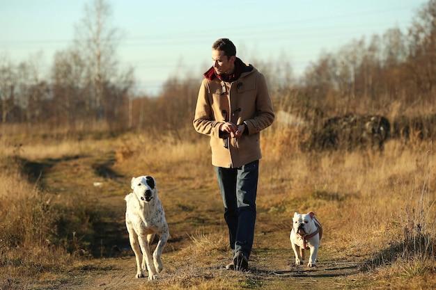 Jovem europeu feliz caminhando em uma estrada rural com dois cachorros bulldog inglês