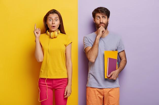 Jovem europeu pensativo segura o queixo, segura caderno e livro didático, pensa em uma lição criativa, mulher impressionada em trajes casuais, aponta o dedo indicador para cima, tem uma ideia inesperada em mente
