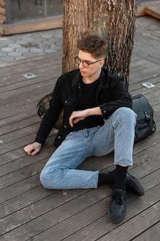 Jovem europeu urbano com óculos vintage e roupas jeans da moda casual