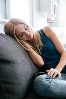Jovem exausta cansada, dormindo no sofá em casa