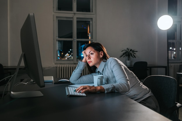Jovem exausta na mesa de escritório, trabalhando tarde da noite.