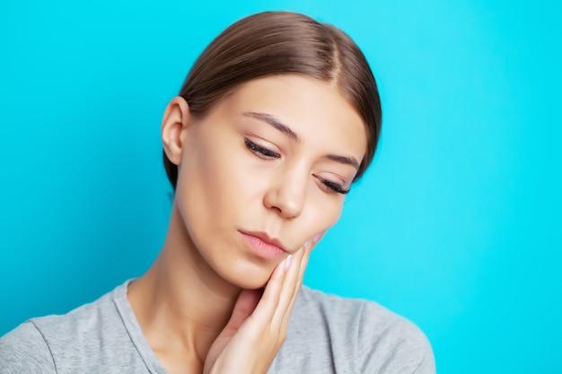 Jovem exausta, sofrendo de dor de dente severa