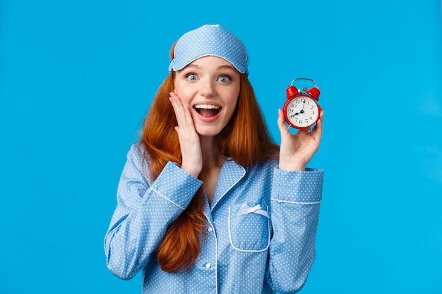 Jovem excitada acorda na hora, segurando o relógio bonito vermelho definir alarme e sorrindo divertido, vestindo roupa de dormir, pijama e máscara de dormir, em pé parede azul otimista