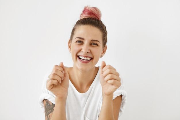 Jovem excitada alegre com braços tatuados e nó de cabelo rosa pastel comemorando seu sucesso e conquista no trabalho, posando com os punhos cerrados, os olhos expressando emoção