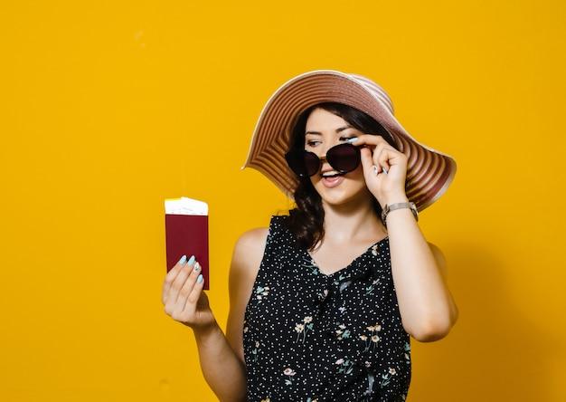 Jovem excitada bonita usando vestido de verão e óculos de sol sstanding isolado sobre parede amarela, mostrando o passaporte com passagens aéreas