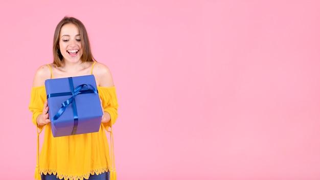 Jovem excitada olhando para caixa de presente embrulhada
