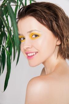Jovem excitada sorrindo com pele perfeita e dentes com maquiagem de cor amarela fresca e planta verde. mulher de beleza natural espantada. expressões faciais expressivas. conceito de tratamento de spa de beleza skincare