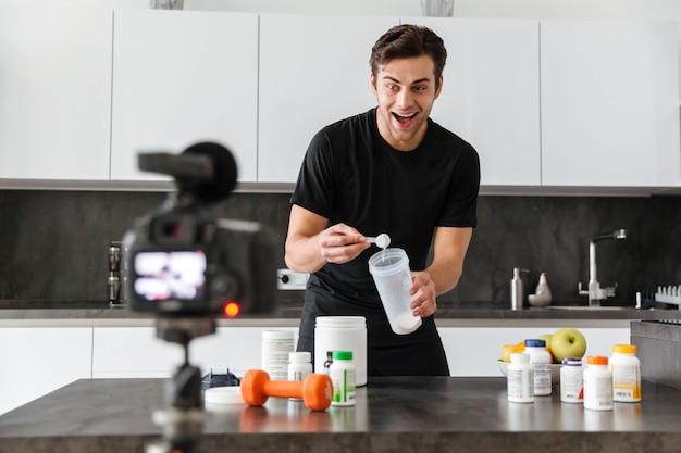 Jovem excitado filmando seu episódio de blog de vídeo