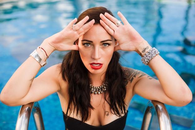 Jovem, excitado, mulher, posar, em, um, piscina, desgastar, pretas, terno natação