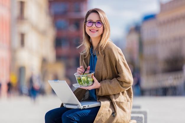 Jovem, executiva, comendo salada, e, trabalhando, com, computador, em, urbano, ao ar livre