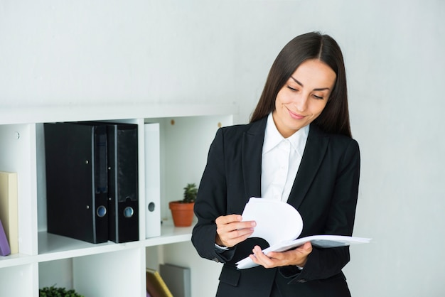Jovem, executiva, examinando, a, documentos, em, escritório