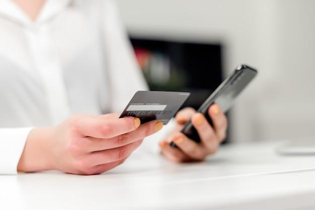 Jovem, executiva, fazer, online, pagamentos, usando, cartão crédito, e, a, telefone, em, escritório